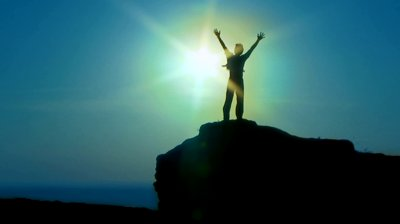 stock-footage-silhouette-man-silhouette-a-man-standing-on-the-edge-of-a-cliff-with-their-hands-up